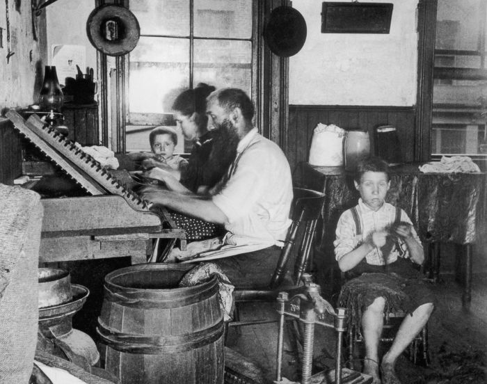 circa 1890: A Bohemian family of four makes cigars at home in their tenement. Working from six in the morning till nine at night, they earn $3.75 for a thousand cigars, and can turn out together three thousand cigars a week. (Photo by Jacob A. Riis/Museum of the City of New York/Getty Images)