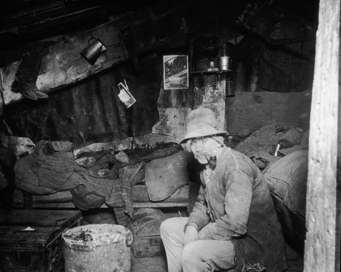 circa 1890: An Italian immigrant man smokes a pipe in his makeshift home under the Rivington Street Dump, New York City. (Photo by Jacob A. Riis/Museum of the City of New York/Getty Images)
